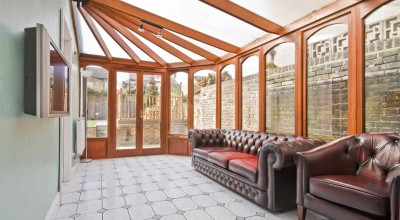 conservatory extension of a family home with leather sofa and tiled floor